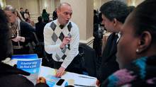 Jason Weinstein, an account manager for Workforce1 Healthcare, discusses job opportunities with attendees at JobEXPO's job fair on Wednesday, Jan. 25, 2012 in New York. (Bebeto Matthews/Bebeto Matthews/AP)