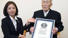 Sakari Momoi, a 111-year-old Japanese retired educator, poses for a photo after receiving a certificate from a Guinness World Records official, left, in Tokyo Wednesday, Aug. 20, 2014. (AP)