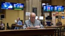 A trader looks at data sheets at the Madrid stock exchange. (PAUL HANNA/REUTERS)