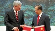Canadian Prime Minister Stephen Harper, left, and Chinese Premier Wen Jiabao are about to shake hands at the end of a signing ceremony held at the Great Hall of the People in Beijing Wednesday, Feb. 8, 2012. Harper was on a five-day trip to China. (AP Photo/Diego Azubel, Pool) (Diego Azubel/AP)