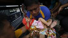 A child, one of the survivors who was evacuated from the disaster zone, is carried into a military truck with her family after they arrive via a military plane at Villamor Air Base in Manila November 12, 2013. (Cheryl Ravelo/REUTERS)