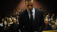 """Oscar Pistorius stands in the dock ahead of court proceedings at the Pretoria magistrates court February 22, 2013. """"Blade Runner"""" Pistorius, a double amputee who became one of the biggest names in world athletics, was applying for bail after being charged in court with shooting dead his girlfriend, 30-year-old model Reeva Steenkamp, in his Pretoria house. (SIPHIWE SIBEKO/Reuters)"""