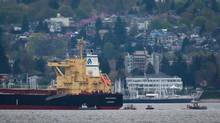 Spill response boats work to clean up bunker fuel that leaked from the bulk carrier cargo ship Marathassa anchored on Burrard Inlet in Vancouver, B.C., on Friday April 10, 2015. (DARRYL DYCK For The Globe and Mail)