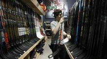 An employee sorts Bauer hockey sticks displayed for sale at an equipment store in Mississauga, Ontario, Canada, on Monday, Oct. 31, 2016. A committee of Performance Sports Group Ltd.'s shareholders has filed a legal objection to a proposed auction of the insolvent company's assets, arguing the bidding structure makes it too hard for anyone to compete with an offer tabled by a group led by Sagard Capital Partners LP. (Cole Burston/Bloomberg)