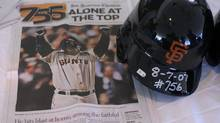 A batting helmet worn by Barry Bonds during his 756th home run, along with a page from the San Francisco Chronicle, is displayed at Albany International Airport in Colonie, N.Y., as it is transported to the National Baseball Hall of Fame and Museum on Thursday, Aug. 9, 2007. (Associated Press)
