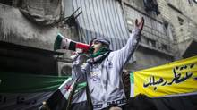 A boy uses a megaphone Friday to lead others in chanting Free Syrian Army slogans during a rally in an Aleppo neighbourhood. (Andoni Lubaki/AP)