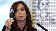 Argentina's President Cristina Fernandez holds up a tube with a sample of the first oil extracted in the country, during her announcement of a bill to nationalize Spain's controlled oil company YPF, at Government House in Buenos Aires, Monday April 16, 2012. Fernandez said in an address to the country that the measure sent to congress on Monday is aimed at recovering the nation's sovereignty over its hydrocarbon resources. (Natacha Pisarenko/AP)