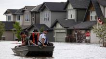 Members of the RCMP return from a boat patrol of a flooded neighborhood in High River, Alta., on July 4, 2013. (JEFF MCINTOSH/THE CANADIAN PRESS)