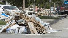 Flood debris piles up on a street in Laval, Que., on May 15, 2017. (Ryan Remiorz/THE CANADIAN PRESS)