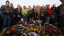 Israelis stand around the grave of former Israeli Prime Minister Ariel Sharon after his funeral near Sycamore Farm, Sharon's residence in southern Israel, January 13, 2014. (Baz Ratner/REUTERS)