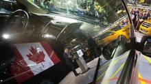 Jerry Dias, national president, Unifor, is reflected in the window of a Ford Edge while he speaks during Ford's official launch of the 2015 Ford Edge production at the assembly plant in Oakville, Ont., on Thursday. (Peter Power For The Globe and Mail)