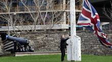 At the end of the day Rene Malagon pulls down the British Flag at Fort York in Toronto on March 23, 2012. The museum will be affected tomorrow if an impending indoor workers city strike is announced. (Michelle Siu for The Globe and Mail)