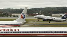 A US Airways plane takes off behind an American Airlines jet at Ronald Reagan National Airport in Washington. (KEVIN LAMARQUE/REUTERS)