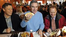 Liberal Leader Michael Ignatieff has a hot dog for lunch with Winnipeg candidates Terry Duguid and Kevin Kevin Lamoureux at Kelekis restaurant on March 31, 2011. (FRED GREENSLADE/REUTERS)