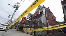 Police tape surrounds the scene of a fatal fire at a rooming house on St Andrews Street in Toronto. Two people have been confirmed dead with more injured in the fire above a Korean restaurant in the Kensington Market. (Fred Lum/The Globe and Mail)