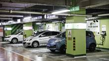 Electric cars sit connected to a charging station operated by Tellus Power Inc. at an underground parking garage in Beijing. By the end of 2015, China had 49,000 public charging points. (Qilai Shen/Bloomberg)