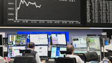 Traders sit at desks and monitor financial data inside the Frankfurt Stock Exchange on Dec. 5, 2016. (Martin Leissl/Bloomberg)