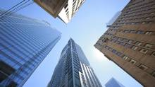"""Corner of Bay Street and Adelaide streets in Toronto, on July 25, 2013. The consumer watchdog charged with overseeing Canada's banks is pledging to publish """"initial findings"""" from a review of sales practices by the end of the year. (Gloria Nieto/The Globe and Mail)"""