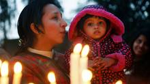 A mother helps her child pray after placing candles at a cathedral in India. (Gurinder Osan/The Associated Press)
