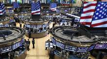Traders work on the floor at the New York Stock Exchange just following the closing bell on March 5. The Dow Jones industrial average soared to a record closing high. (BRENDAN McDERMID/REUTERS)
