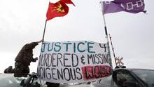 Native protesters rise a banner during a blockade at the VIA train tracks and Wyman's Road near Shannonville, Ont., on Wednesday March 19, 2014. The protesters want justice for murdered and missing indigenous women. (Lars Hagberg/The Canadian Press)