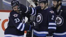 Winnipeg Jets' Dustin Byfuglien (33) and Adam Pardy (2) celebrate Byfuglien's overtime goal to beat the Toronto Maple Leafs 5-4 in NHL action in Winnipeg on Saturday, January 25, 2014. (JOHN WOODS/THE CANADIAN PRESS)