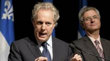 Quebec Premier Jean Charest, left, announces a commission of inquiry in the construction industry Wednesday, October 19, 2011 in Quebec City. (Jacques Boissinot/Jacques Boissinot/THE CANADIAN PRESS)