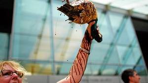 Consumer advocate Barbara Holzer holds up a model duck coated in chocolate syrup made to look like oil at a protest outside BP's offices in Washington.
