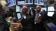 Goldman Sachs floor governor Henry Becker Jr. (C) and NYSE floor manager Rudy Mass (centre, R) determine bids for Grainger at the post that trades it on floor at the New York Stock Exchange. (BRENDAN MCDERMID/REUTERS)