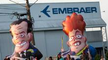 Workers of Embraer's aircraft factory protest against Brazil's President Dilma Rousseff, former president Luiz Inacio Lula da Silva and opposition as they carry inflatable dolls depicting Rousseff and opposition senator Aecio Neves, in front of the plant in Sao Jose dos Campos, Brazil, March 21, 2016. (ROOSEVELT CASSIO/REUTERS)