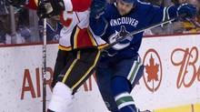 Calgary Flames defenseman Cory Sarich fights for control of the puck with Vancouver Canucks right wing Zack Kassian (JONATHAN HAYWARD/The Canadian Press)