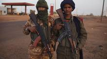 Ethnic Tuareg Malian soldiers pose for a picture at a checkpoint in Gao on March 3, 2013. Heavy fighting in northern Mali has left at least 50 rebel fighters and a French soldier dead. (JOE PENNEY/REUTERS)