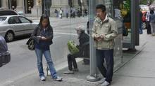 Transit riders use their smartphones while waiting for an eastbound streetcar in downtown Toronto on Sept. 13, 2013. (Fred Lum/The Globe and Mail)