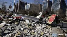 A handicapped man searches for recyclable materials in garbage piled along a roadside in Beijing. The city's 20 million residents produce 23,000 tonnes of waste a day, the byproduct of a growing middle class. (Ng Han Guan/Associated Press/Ng Han Guan/Associated Press)