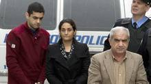 Mohammad Shafia, Tooba Yahya and their son Hamed Shafia are escorted into the Frontenac County courthouse in Kingston, Ont., January 26, 2012. (Frank Gunn/THE CANADIAN PRESS)