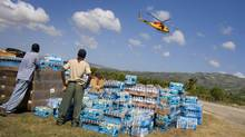 Bottled water sits near the tarmac at the airport in Jacmel, Haiti, in January, 2010, waiting to be loaded onto trucks and taken to a warehouse. A Canadian helicopter flies overhead. (PETER POWER/THE GLOBE AND MAIL)