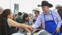 Prime Minister Stephen Harper shakes hands with a woman while serving pancakes during the Calgary Stampede in Calgary, Alberta, in this file photo taken July 4, 2015. Speculation mounted on Thursday that Canada's election campaign would formally begin on Sunday, with the governing Conservatives planning a Montreal rally with Prime Minister Stephen Harper on Sunday evening. (STRINGER/REUTERS)