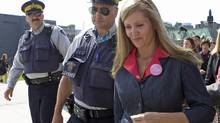 With RCMP officers keeping a throng of reporters at bay, status of women Helena Guergis leaves Parliament Hill on Sept. 17, 2009. (Sean Kilpatrick/The Canadiand Press)