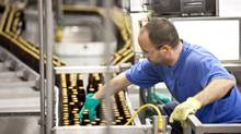 A worker inspects bottles on the production line at Labatt London Brewery in its London facility. (GEOFF ROBINS For The Globe and Mail)