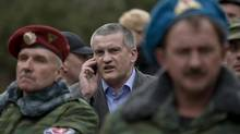 "In this Saturday, March 8, 2014 file photo, Sergei Aksyonov, center, speaks on a mobile phone as he attends the swearing in ceremony for the first unit of a pro-Russian armed force, dubbed the ""military forces of the autonomous republic of Crimea"" in Simferopol, Ukraine. (Vadim Ghirda/AP)"