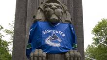 A statue at the entrance to the Lions Gate Bridge wears a Vancouver Canucks jersey in Vancouver, British Columbia May 25, 2011. The NHL team advanced to the Stanley Cup Final for the first time in 17 years. (ANDY CLARK/REUTERS)