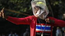 An anti-government protester uses a slingshot to throw rocks at Thai riot police as they attack the Thai-Japan youth stadium in central Bangkok on Dec. 26, 2013. (ATHIT PERAWONGMETHA/REUTERS)