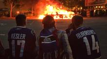 Vancouver Canucks fans watch police cars burn after Game 7 of the NHL Stanley Cup hockey playoff (ANDY CLARK)
