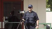 An RCMP officer videotapes a protest against Enbridge's proposed Northern Gateway pipeline gather outside the Joint Review final argument hearings in Terrace, B.C., on Monday June 17, 2013. (Robin Rowland/THE CANADIAN PRESS)
