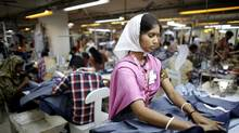 Employees work in a factory of Babylon Garments in Dhaka January 3, 2014. No matter which brand they happen to be sewing for, workers should expect minimum standards for safety at work. (© Andrew Biraj / Reuters/REUTERS)