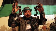Uthman Suleiman, 32, who describes himself as a security chief for the rebel city of Al Bayda, holds up war trophies captured from pro-Gadhafi fighters in the early days of the revolution. (Graeme Smith for The Globe and Mail)