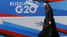 A Russian Orthodox priest walks past a banner for the G20 summit in St. Petersburg, Russia. (DMITRY LOVETSKY/AP)