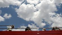 Tourists board a double decker tour bus at the foot of the CN Tower on Front St. West. (Fred Lum/The Globe and Mail)
