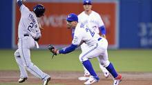 Devon Travis, right, chases down Nick Franklin to get the first out of a double play during second inning on Tuesday. (Frank Gunn/THE CANADIAN PRESS)