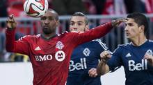 Toronto FC forward Jermain Defoe, left, battles for the ball against Vancouver Whitecaps defender Johnny Leveron, right, during first half semi-final Amway Canadian Championship soccer action in Toronto on Wednesday, May 7, 2014. (Nathan Denette/THE CANADIAN PRESS)